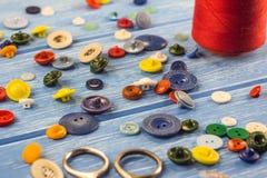 Threads und Knöpfe auf einem blauen hölzernen Hintergrund Dressmaking lizenzfreies stockbild