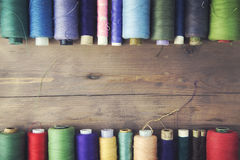 Threads on wooden table. Bobbins with colorful threads on old wooden table background Royalty Free Stock Photo