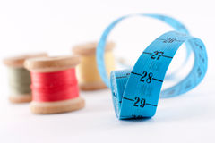 Threads and yardstick. Colored bobbin threads and blue yardstick on wite Royalty Free Stock Photography