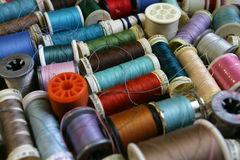 Threadscape background. Colourful background assortment of bobbins and spools of thread. Shallow depth of field - focus in the middle stock images