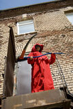 Threat from above. Girl in red hood with a scythe making a threatning swing from above royalty free stock photo