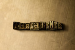 THREATENED - close-up of grungy vintage typeset word on metal backdrop Royalty Free Stock Photo