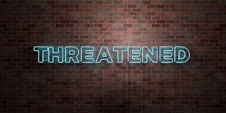 THREATENED - fluorescent Neon tube Sign on brickwork - Front view - 3D rendered royalty free stock picture Royalty Free Stock Photos