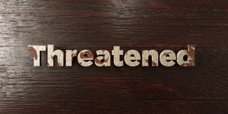 Threatened - grungy wooden headline on Maple  - 3D rendered royalty free stock image Royalty Free Stock Images