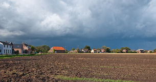 Threatening clouds over a plowed field in autumn Royalty Free Stock Photos