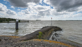 Threatening clouds and stormy weather. Breakwater in the waves and ripples of a Dutch river during stormy weather Royalty Free Stock Photos