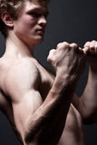 Threatening gesture. The young brawny man to prepare for fight. Focus on a fist Royalty Free Stock Photography