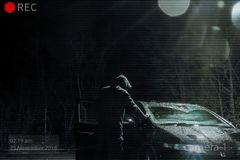A threatening hooded man looking into a car at night. Photoshop edit to look like CCTV image.  royalty free stock photos