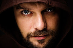 Threatening man with beard wearing a hood. Close-up portrait of threatening man with beard wearing a hood royalty free stock images