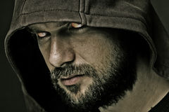Threatening man with beard wearing a hood. Close-up portrait of threatening man with beard wearing a hood Stock Images