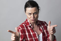 Threatening middle aged woman provoking with aggressive hand gestures. With fingers shooting like guns in the foreground Royalty Free Stock Photos