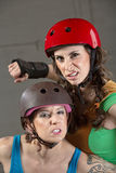Threatening Roller Derby Skaters. Two tough female roller derby skaters with clenched teeth Stock Image