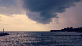 Threatening storm clouds over lake. Threatening storm clouds over the lake with a view of a distant shore and a pier in a middle ground Stock Photos