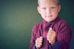 Threatening 5-year old boy looking violent with fists in the forefront, acting like a little bully at school, contrast. Effects over green background stock image