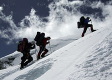 Three. Mountaineers with backpacks climbing a snowy ridge Royalty Free Stock Photos