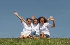 Three. Nice young girls sit on a grass on a background of the blue sky, smile and wave hands Stock Photo