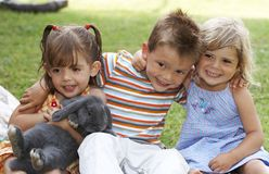 Three. Young kids with a rabbit smiling Royalty Free Stock Image