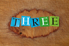Three. Text on a wooden board royalty free stock photos