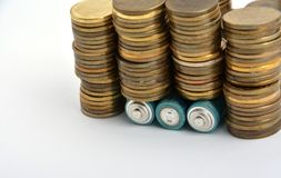 Three AAA batteries with coins isolated on white. Background Royalty Free Stock Images