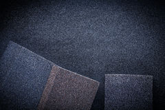 Three abrasive sponges on sandpaper Royalty Free Stock Photos