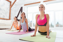 Three active girls doing stretching after group workout. Let your body rest. Three active young girls doing stretching after having group workout while relaxing royalty free stock images