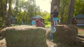 Three active little girls playing in hay and haystacks together. They climb on and jump off haystacks to entertain themselves. Slow motion stock video footage