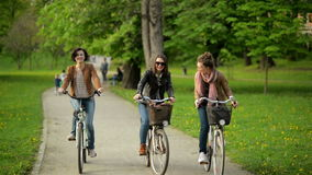 Three Active Young Women are Riding Together in the City Park. Smiling Brunettes with Bicycles Outdoors. Three Active Young Women are Riding Together in the stock video