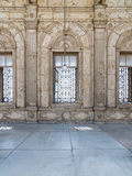 Three adjacent arched windows with decorated iron grid over white marble decorated wall Royalty Free Stock Photo