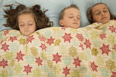 Three adorable children asleep under a snowflake blanket Royalty Free Stock Images