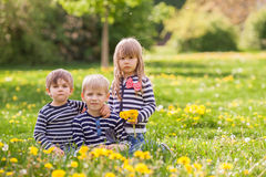 Three adorable kids, dressed in striped shirts, hugging and smil Royalty Free Stock Photos