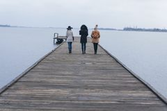 Three adult girls walk towards the lake royalty free stock images