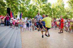 Three adult men at the same time jumping over rope which girls in pirate costumes hold at pirate party. Komsomolsk-on-Amur, Russia - August 1, 2016. Public open royalty free stock image
