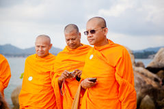 Three adult monk tourist wearing glasses and a orange dress with a camera and a phone in Thailand on Koh Samui Stock Images