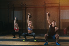 Three adults doing squats with kettle bells Stock Photography