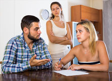Three adults with papers. Young adults explaining contract terms to friend at the table. Selective focus Stock Images