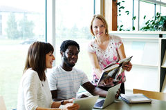 Three adults pouring over books and computer Stock Images