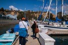 Three adults walking away on a dock past boats stock images