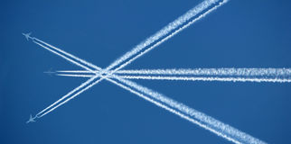 Three aeroplanes and contrails. Photo of three jet aeroplanes crossing each other and their contrails Stock Photo