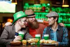 Companions in pub. Three affectionate companions celebrating Saint Patrick day in irish pub Stock Photos