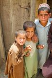 Three Afghan Kids Watch an ISAF Patrol Stock Image