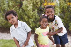 Three African American kids in a garden looking to camera stock photo