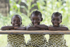 Three African children sitting outdoors smiling and laughing. Two young african girls and boy sitting at wooden table and smiling at camera Royalty Free Stock Images