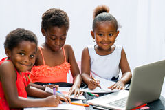 Three African fiends spending time together drawing. stock images