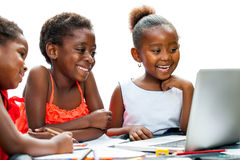 Three African kids laughing at scene on laptop. Royalty Free Stock Images