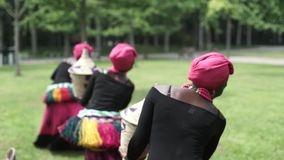 Three african women dancing folk dance in traditio.costumes with coats of skirts