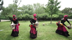 Three african women dancing a folk dance in traditional costumes with wicker baskets