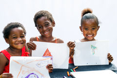 Three African youngsters showing their drawings. Portrait of three African youngsters showing their drawings at desk.Isolated on light background royalty free stock images