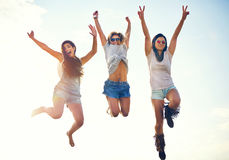 Three agile energetic teenagers leaping in the air. Three agile energetic teenage girls leaping in the air laughing and cheering with extended arms as they royalty free stock photos