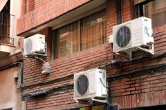 Three air conditioning units on the outside red brick wall of a. Domestic apartment building royalty free stock photography
