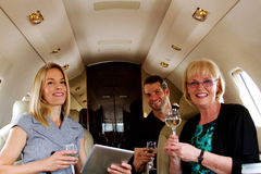 Three airline passengers with drinks Stock Image